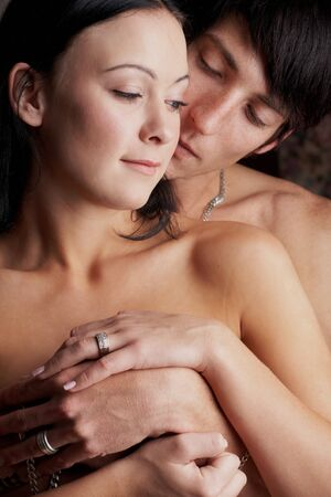 Young adult Caucasian couple in passionate embrace and undressing each other during ual foreplay Stock Photo - 3233469