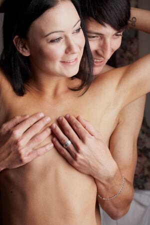 Young adult Caucasian couple in passionate embrace and undressing each other during ual foreplay Stock Photo - 3233409