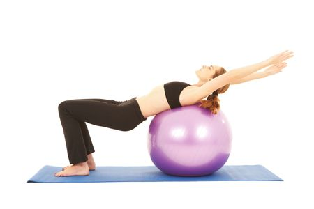 instruct: Fit young brunette pilates instructor showing different exercises on a white background with basic pilates equipment including a ball and yoga mat. White background, not isolated