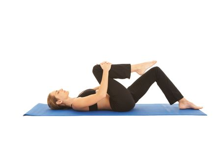muscle toning: Fit young brunette pilates instructor showing different exercises on a white background a blue yoga mat. White background NOT ISOLATED