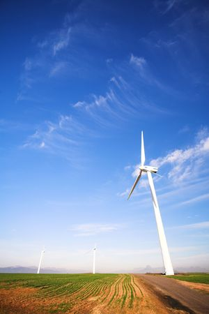 electricity generator: Wind powered electricity generator standing against the blue sky in a green field on the wind farm. A man is walking past the first generator