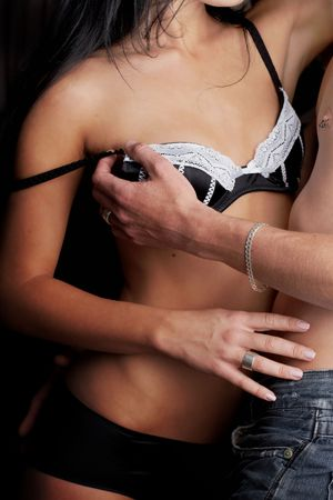 Young adult Caucasian couple in passionate embrace and undressing each other during ual foreplay