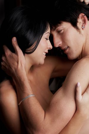 Young adult Caucasian couple in passionate embrace and undressing each other during sexual foreplay