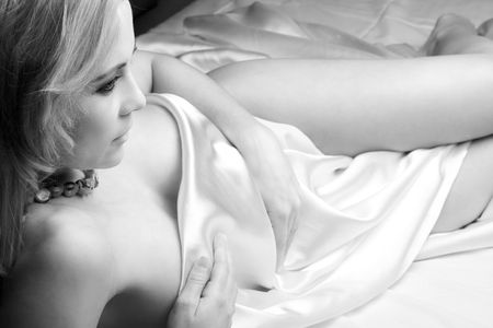 Sensual  young blonde adult Caucasian woman, wrapped in a satin, silk sheet on a bed in her bedroom. High contrast lighting in Black and White