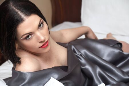 Sensual  young Black haired adult Caucasian woman, wrapped in a charcoal colored satin, silk sheet on a bed in her bedroom. High contrast lighting.
