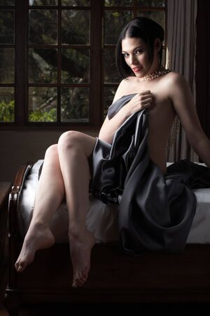 Sensual  young Black haired adult Caucasian woman, wrapped in a charcoal colored satin, silk sheet on a bed in her bedroom. High contrast lighting. Stock Photo - 3491587