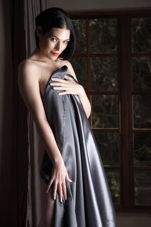 Sensual  young Black haired adult Caucasian woman, wrapped in a charcoal colored satin, silk sheet on a bed in her bedroom. High contrast lighting. Stock Photo - 3491584