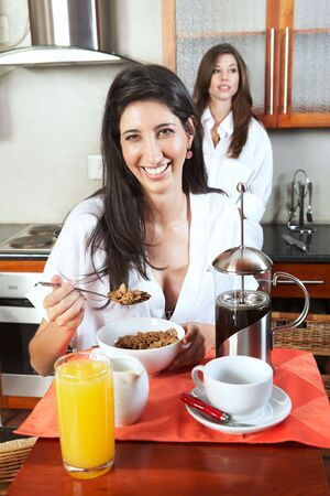 Sexy young adult brunette roommates in lingerie eating breakfast and drinking coffee in their kitchen before work Stock Photo - 3491662