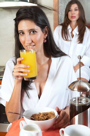 Sexy young adult brunette roommates in lingerie eating breakfast and drinking coffee in their kitchen before work Stock Photo - 3491642