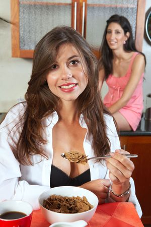 Sexy young adult brunette roommates in lingerie eating breakfast and drinking coffee in their kitchen before work Stock Photo - 3491606