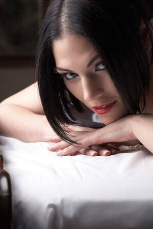 Sensual  young black haired adult Caucasian woman, lying on a bed high key image. Stock Photo - 3491564