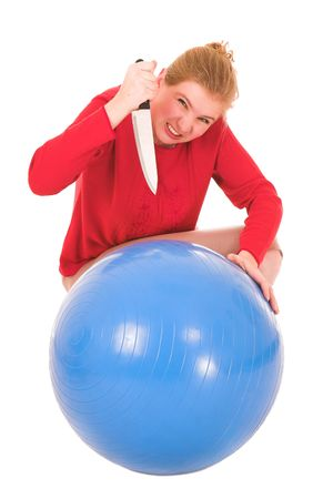 Frustrated blonde middle aged woman with a large carving knife about to kill a yoga ball