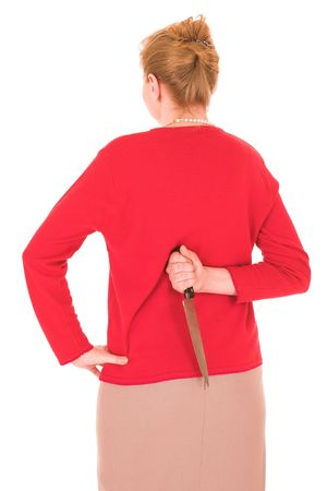 Blonde middle aged woman with a large carving knife hidden behind her back against a white background