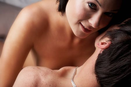 Young adult Caucasian couple in passionate embrace and undressing each other during sexual foreplay. The woman is wearing blue contact lenses