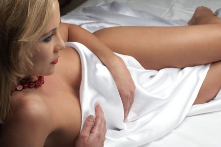Sensual  young blonde adult Caucasian woman, wrapped in a satin, silk sheet on a bed in her bedroom. High contrast lighting. Stock Photo