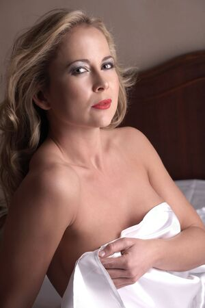 Sensual  young blonde adult Caucasian woman, wrapped in a satin, silk sheet on a bed in her bedroom. High contrast lighting. Stock Photo - 3646171