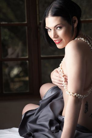 Sensual naked young Black haired adult Caucasian woman, wrapped in a charcoal colored satin, silk sheet on a bed in her bedroom. Fresh water pearl necklace