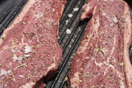 Raw steaks being prepared in a black cast iron skillet photo