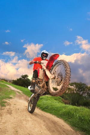 mx: Young man riding around on his dirtbike doing tricks and getting dirty. Movement on edges of motorbike