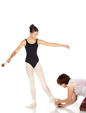Young caucasian ballerina girl on white background and reflective white floor showing various ballet steps and positions being corrected by teacher. Not Isolated.