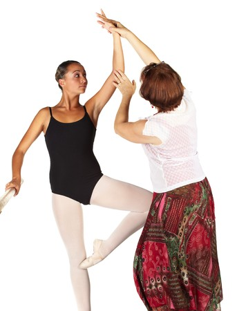 Young caucasian ballerina girl on white background and reflective white floor showing various ballet steps and positions, being corrected by teacher. Not Isolated.