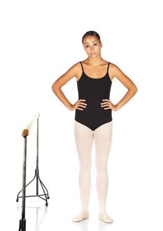 Tired young caucasian ballerina girl on white background and reflective white floor next to a barre. Not Isolated. photo