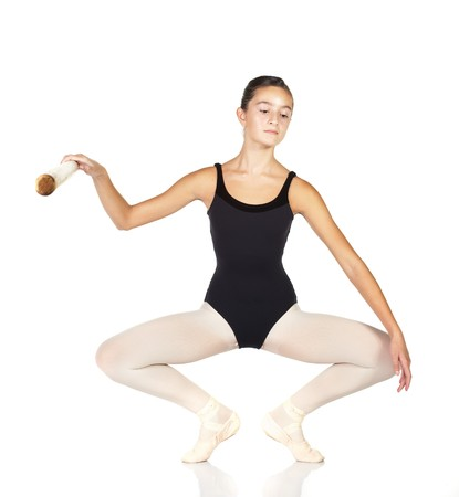 Young caucasian ballerina girl on white background and reflective white floor showing various ballet steps and positions. Full Plie in first Position.  Not Isolated. Stock Photo