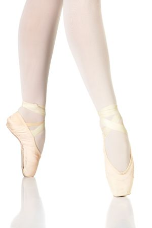 Young female ballet dancer showing various classic ballet feet positions on Pointe against a white background - 4th position en pointe. NOT ISOLATED photo