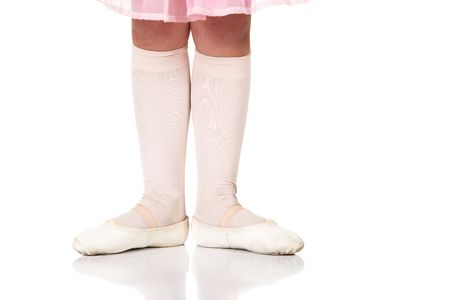 beginner: Young female ballet dancer showing various classic ballet feet positions on a white background - Beginner 1st position. NOT ISOLATED