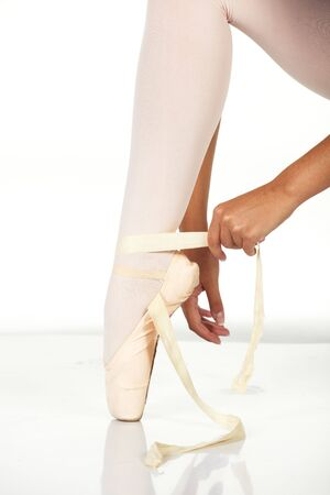 tying: Young female ballet dancer showing how to tie a ballet Pointe Shoe against a white background. NOT ISOLATED