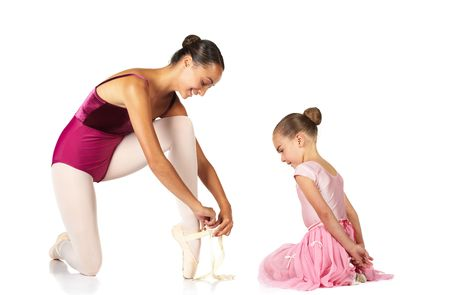 tying: Young female ballet dancer showing a young dancer how to tie a ballet Pointe Shoe against a white background. NOT ISOLATED Stock Photo