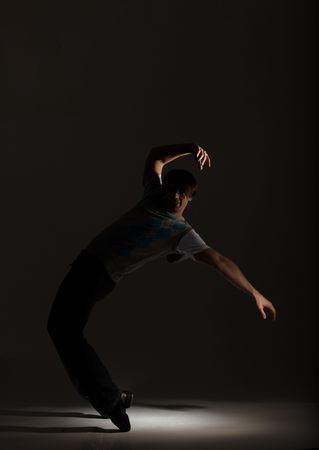 tap dance: Young male tap dancer on his toes in the spotlight