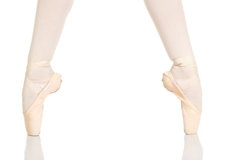 pointe: Young caucasian ballerina girl on white background and reflective white floor showing various ballet steps and positions. Not Isolated