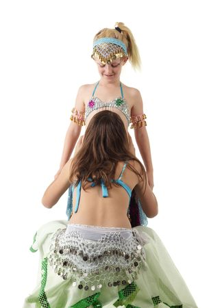 Two young Caucasian belly dancing girls in beautiful decorated clothes on white background. Not isolated Stock Photo - 5275249