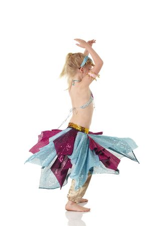 Young Caucasian belly dancing girl in beautiful decorated clothes on white background and reflective floor. Not isolated Stock Photo