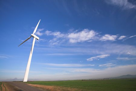 electricity generator: Wind powered electricity generator standing against the blue sky in a green field on the wind farm Stock Photo
