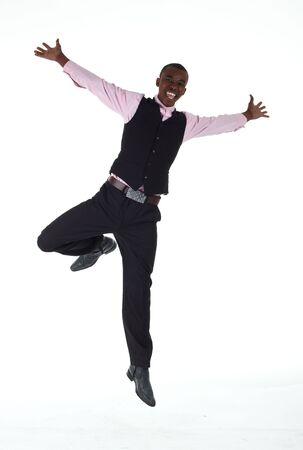 salto largo: J�venes adultos negros empresario africano, vistiendo un traje oscuro de inteligentes-casual sin una chaqueta, pero con una camiseta rosa y un chaleco oscuro, saltando alrededor sobre un fondo blanco en varias poses con diversas expresiones faciales. Parte de una serie, no aislado. Foto de archivo