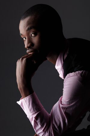 Young Adult black african businessman wearing a dark smart-casual outfit without a Jacket, but with a pink shirt and a dark waistcoat on a dark grey background in various poses with various facial expressions. Part of a series, Not Isolated. Single lights photo