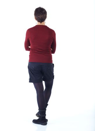Cute young adult caucasian woman with short hair in a red top, black shorts and stockings on a white background in various poses, with various facial expressions. Not Isolated Stock Photo