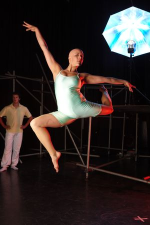 bald girl: A group of female and male freestyle hip-hop dancers during dance training session on stage. Lit with spotlights