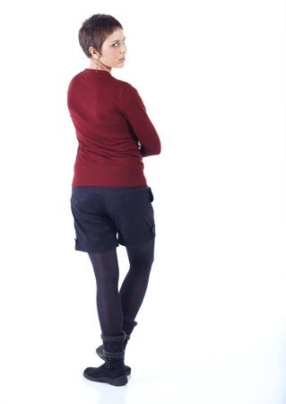 woman from behind: Cute young adult caucasian woman with short hair in a red top, black shorts and stockings on a white background in various poses, with various facial expressions. Not Isolated Stock Photo