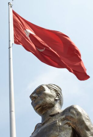 signifies: Monument of Ataturk and Youth, Kusadasi, Turkey with a Turkish flag in the background. The monument signifies peace and hope
