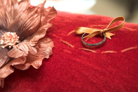 unpretentious: Fine wedding ring tied to a red velvet ring-bearers cushion with a golden bow and bronze material flower. Shallow Depth of Field, focus on the ring Stock Photo