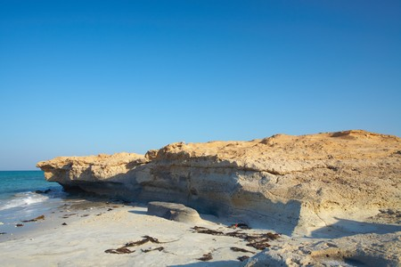 persian gulf: A sandstone beach on the edge of the desert at the northern coast of Qatar in the Middle East, Persian Gulf Stock Photo