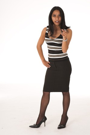 pencil skirt: Young adult African-Indian businesswoman in casual office outfit with a black pencil skirt, a striped brown top and high heels on a white background. Not Isolated