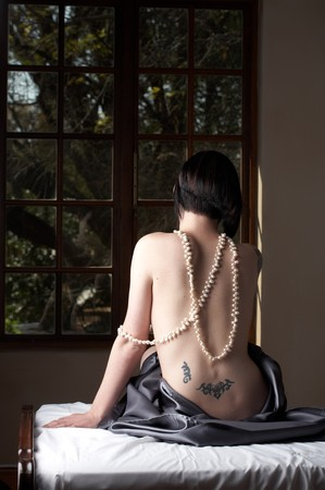 Sexy naked young caucasian adult woman with short black hair and covered in a dark satin sheet, sitting on a bed with her back to the camera and wearing a string of pearls photo