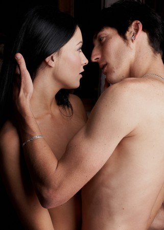 Young adult Caucasian couple in passionate embrace and undressing each other during sexual foreplay Stock Photo - 7783196