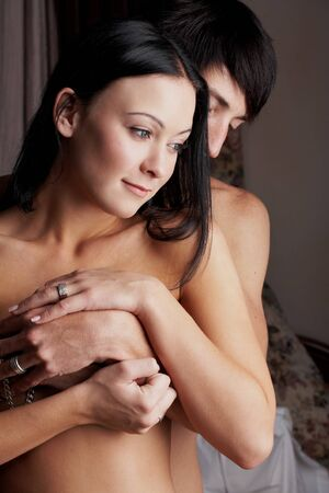 Young adult Caucasian couple in passionate embrace and undressing each other during sexual foreplay photo