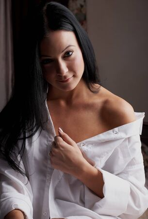 boudoir: Young brunette caucasian woman wearing a white mans shirt sitting in her bedroom