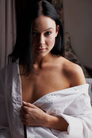Young brunette caucasian woman wearing a white mans shirt sitting in her bedroom photo